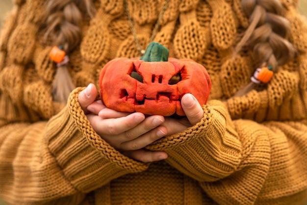 Dziecko trzyma małą dynię na halloween