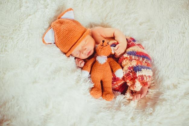 Dziecko trzyma małego lisa zabawkarskiego dosypianie na białej poduszce