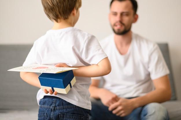 Dziecko trzyma niespodziankę dla ojca