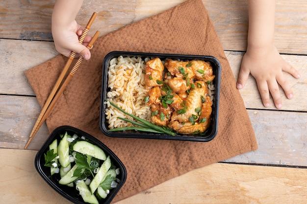 Dziecko trzyma pałeczki do jedzenia. azjatycki makaron z brokułami, papryką, pieczarkami i kurczakiem w plastikowych pudełkach, widok z góry