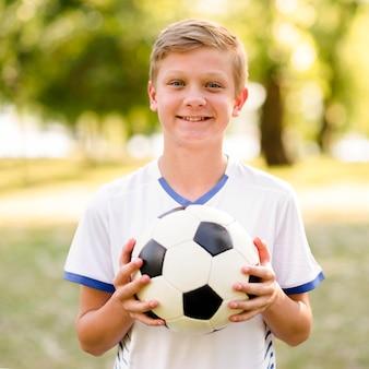 Dziecko trzyma piłkę nożną na zewnątrz
