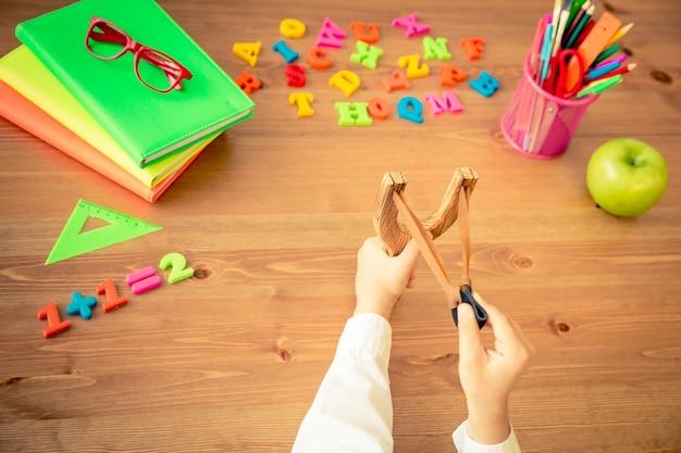 Dziecko trzyma procę w rękach. przedmioty szkolne na drewnianym biurku w klasie. koncepcja edukacji. widok z góry