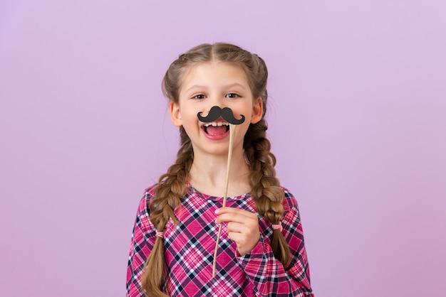 Dziecko trzyma przy twarzy czarne wąsy w stylu maskarady.
