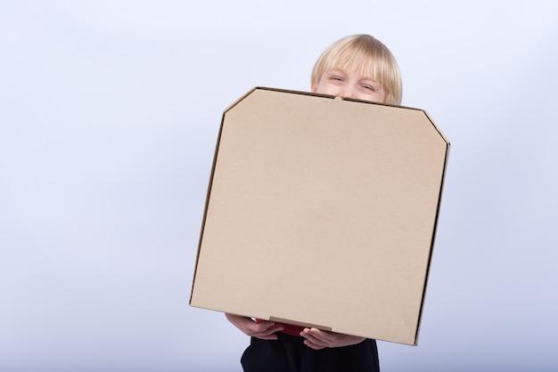 Dziecko trzyma pudełko pizzy i śmieje się. jasnowłosy z pudełkiem w rękach. dostawa pizzy