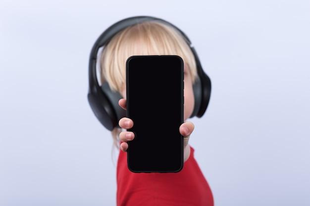 Dziecko trzyma telefon komórkowy. smartphone z bliska z czarnym wyświetlaczem
