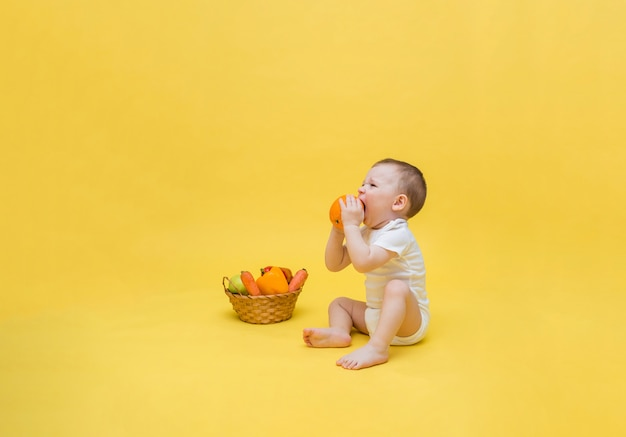 Dziecko trzyma w dłoni pomarańczę i skrzywi się na kwaśny smak. mały chłopiec siedzi z koszem warzyw i owoców. skopiuj miejsce
