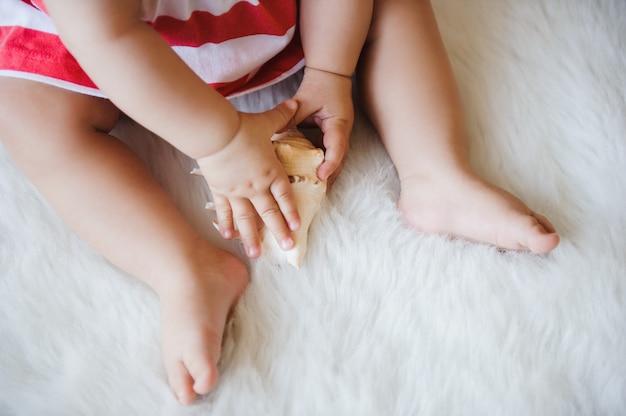 Dziecko trzyma w dłoniach muszlę.