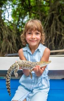 Dziecko trzyma w rękach małego krokodyla.