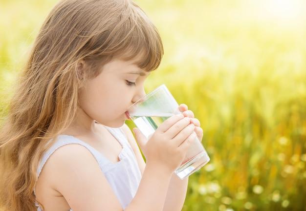 Dziecko trzyma w rękach szklankę wody. selektywna ostrość.