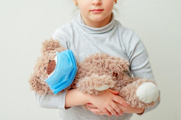Dziecko trzyma zabawkowego niedźwiedzia w medycznej masce