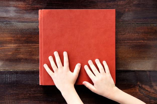 Dziecko, trzymając się za ręce na brązowy skórzany album ślubny lub książki