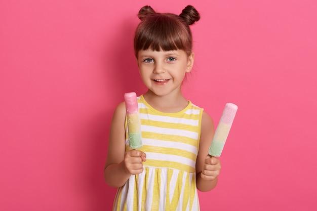 Dziecko trzymające dwa lody, szczęśliwa mała dziewczynka ciesząca się lodem wodnym, słodkie dziecko degustujące pyszne uliczne potrawy latem, pozowanie na różowej ścianie.