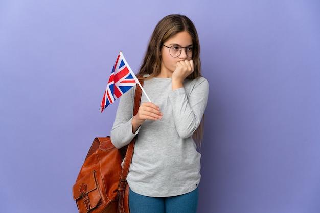 Dziecko trzymające flagę wielkiej brytanii na białym tle, które ma wątpliwości