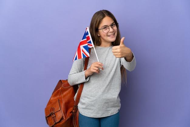 Dziecko trzymające flagę zjednoczonego królestwa na odizolowanej ścianie z kciukami do góry, ponieważ wydarzyło się coś dobrego