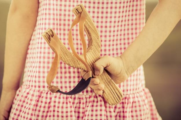 Dziecko trzymające procę w ręku