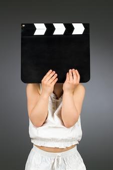 Dziecko trzymające pustą deskę klapy z copyspace
