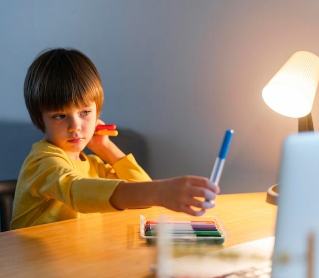 Dziecko trzymające w ręku niebieski marker