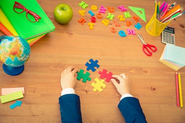 Dziecko trzymające wielokolorowe puzzle w rękach przedmioty szkolne na drewnianym biurku w klasie koncepcja edukacji