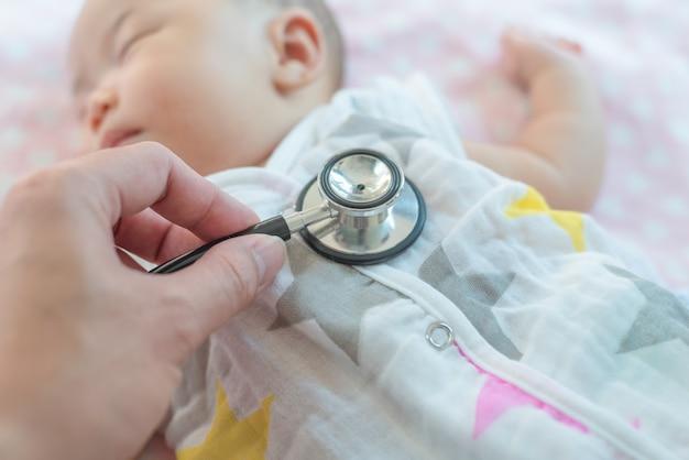 Dziecko u lekarza zaczyna sprawdzać oddech stetoskopem.