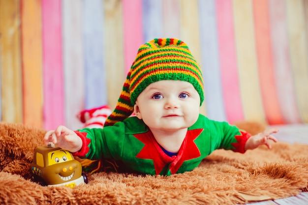 Dziecko ubrane jak elf leży na puszystym dywanie