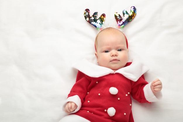Dziecko ubrane na pierwsze boże narodzenie z dekoracją świąteczną na białym tle.