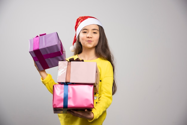 Dziecko ubrane w czerwony kapelusz świętego mikołaja, niosący wiele prezentów świątecznych. wysokiej jakości zdjęcie