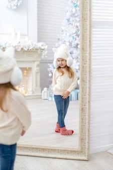 Dziecko ubrane w dzianinowe ubrania. słodka dziewczyna w kapeluszu sweterku i wełnianych skarpetkach podziwia siebie w lustrze. rama pionowa. dziewczynka ma 4 lata. jasny pokój z choinką