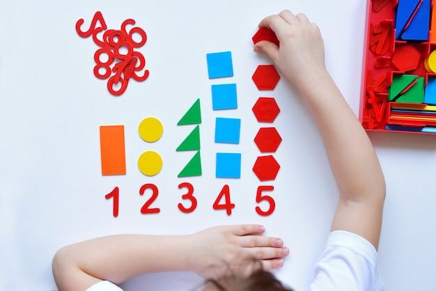 Dziecko Uczy Się Linii Liczbowej I Kształtów Geometrycznych. Przedszkolak Pracuje Z Materiałem Montessori. Premium Zdjęcia