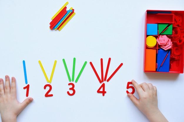 Dziecko uczy się linii liczbowej i kształtów geometrycznych. przedszkolak pracuje z materiałem montessori.