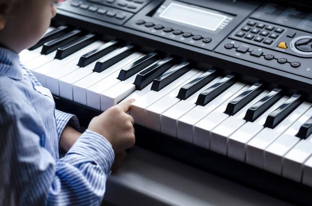 Dziecko uczy się muzyki na pianinie. dziewczyna gra na klawiszach.