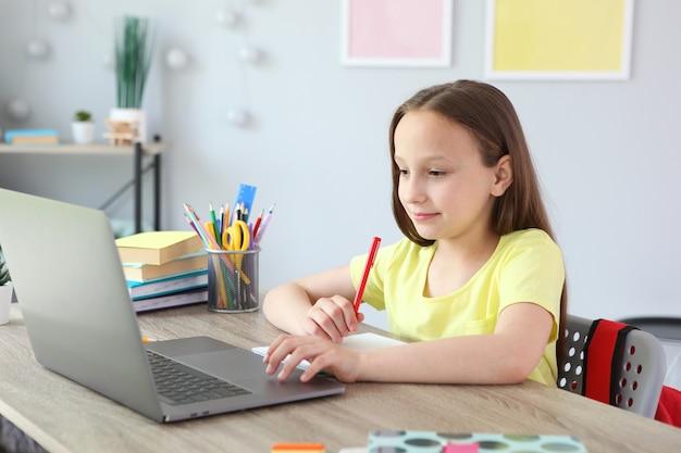 Dziecko uczy się online w domu za pomocą nowoczesnego laptopa w internecie