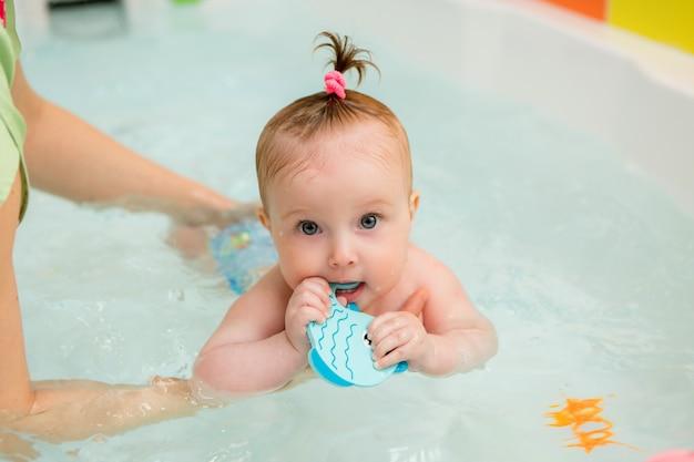 Dziecko uczy się pływania, pływanie dla niemowląt, zdrowa rodzina matka nauczanie basen dla dzieci