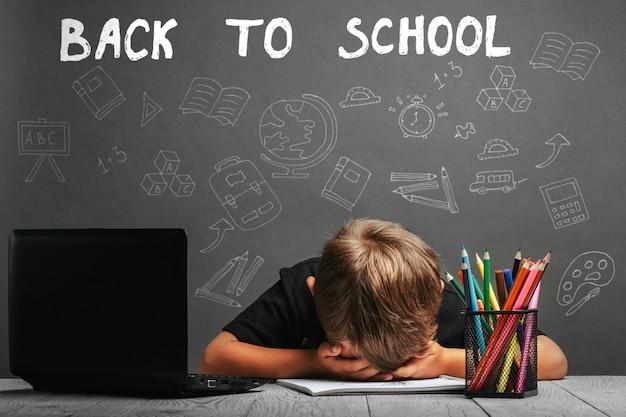 Dziecko uczy się zdalnie w szkole, nosząc kask astronauty. powrót do szkoły