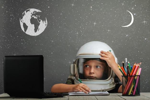 Dziecko uczy się zdalnie w szkole, ubrane w hełm astronauty. powrót do szkoły. usterka efektów