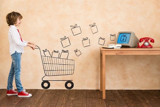 Dziecko udaje biznesmena. dziecko bawiące się w domu. wyobraźnia i koncepcja e-zakupów. skopiuj miejsce na swój tekst