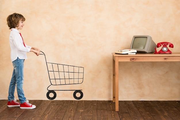 Dziecko udaje biznesmena. dziecko bawiące się w domu. wyobraźnia, pomysł i koncepcja e-zakupów. skopiuj miejsce na swój tekst