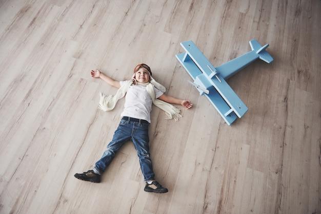 Dziecko udaje pilota. dzieciak ma zabawę w domu. letnie wakacje i podróże. widok z góry