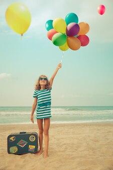 Dziecko udaje żeglarza szczęśliwe dziecko bawiące się na świeżym powietrzu na plaży dziewczyna przed morzem i niebem koncepcja letnich wakacji i podróży
