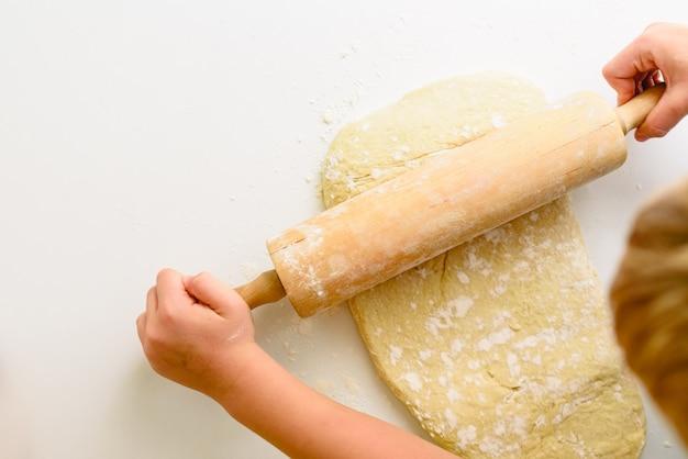Dziecko ugniatając ciasto z pizzy, oglądane z góry.