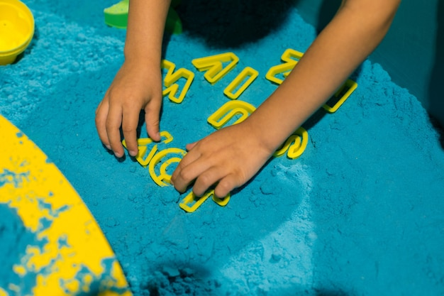 Dziecko układa słowo radość z piasku kinetycznego. łagodzi stres i napięcie. wrażenia dotykowe. kreatywność i przyjemność. rozwój umiejętności motorycznych. koncentracja i uwaga.