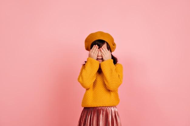 Dziecko ukrywa twarz na różowej ścianie.