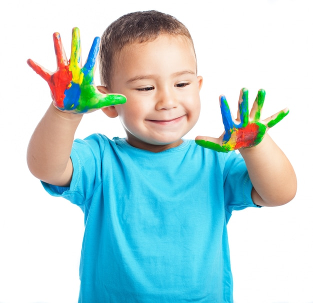 Dziecko uśmiecha się z rękami pełnymi farby