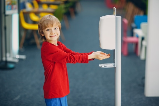 Dziecko uśmiechnięte dziecko chłopiec za pomocą automatycznego dozownika żelu alkoholu rozpylającego na ręce