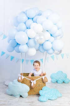 Dziecko w balonie, lot małego dziecka w niebieskim balonie