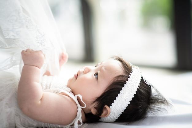 Dziecko w białej sukni ciągnie biały koc.