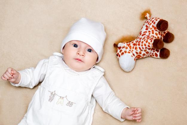 Dziecko w białym garniturze leży na plecach na beżowym dywanie, obok miękkiej zabawki