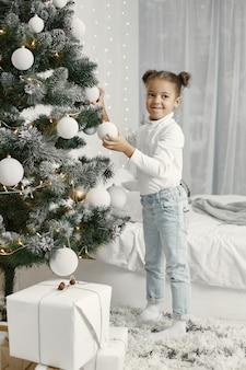 Dziecko w białym swetrze. córka stojąca w pobliżu choinki.