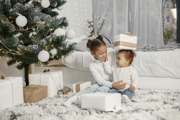 Dziecko w białym swetrze. córki jadą w pobliżu choinki. dwie siostry w domu.