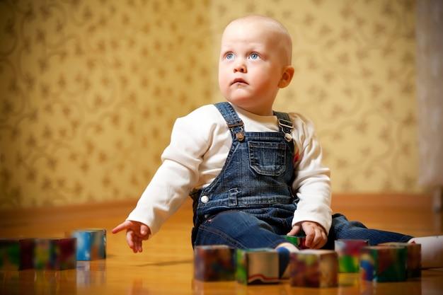 Dziecko w białym swetrze i jeansowym kombinezonie