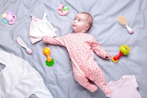 Dziecko w bieli z ubraniami, kosmetykami, zabawkami i akcesoriami do opieki zdrowotnej. lista życzeń lub przegląd zakupów na ciążę i baby shower.